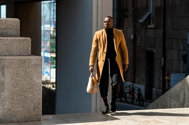 Uomo bello nero in abiti eleganti ed eleganti che camminano in fretta tenendo in mano una borsa. vita di città e stile di vita urbano.