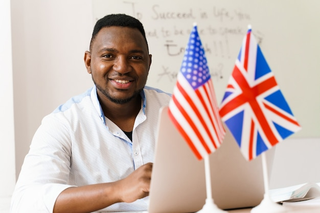 Il bell'uomo nero utilizza il suo laptop per il lavoro online in base alle distanze sociali Foto Premium