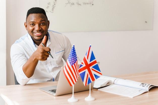 Il bel traduttore nero usa il suo laptop per il lavoro online in base alle distanze sociali