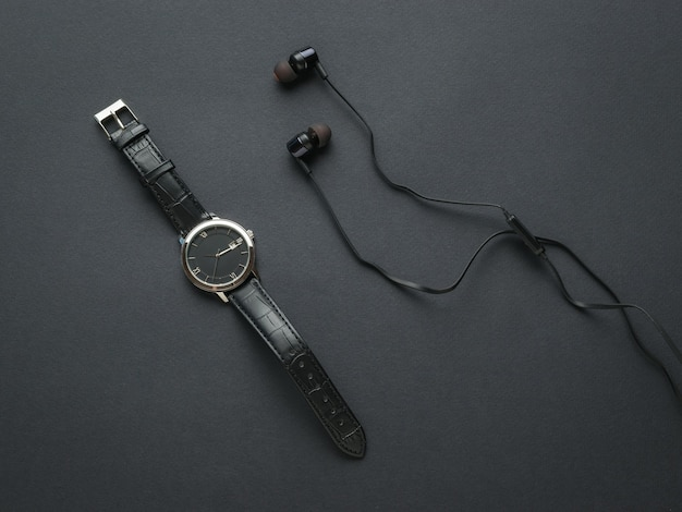 Cuffie nere e un orologio da uomo nero su sfondo nero. accessori moda uomo.