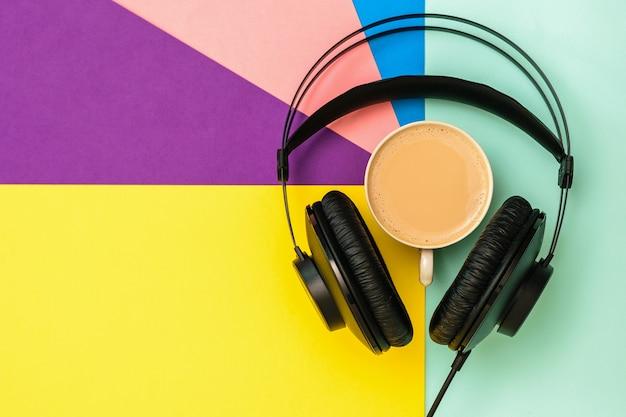 Cuffie nere e una tazza di caffè su uno sfondo colorato. attrezzatura per la registrazione di brani musicali. la vista dall'alto. lay piatto.