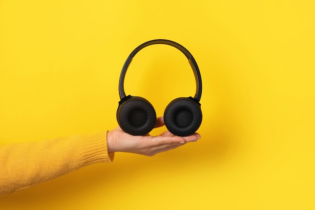 Cuffie nere a portata di mano su sfondo giallo