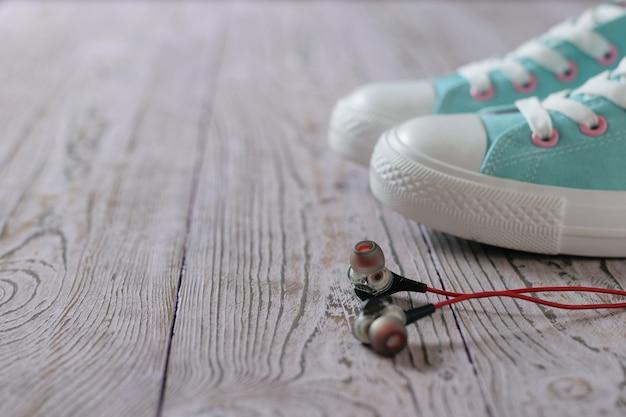 Cuffie nere con filo rosso sul pavimento accanto a scarpe da ginnastica turchesi. stile sportivo.