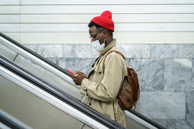 L'uomo nero dei pantaloni a vita bassa si leva in piedi sulla mascherina di usura della scala mobile utilizzando il cellulare. virus influenzale, corona covid-19.