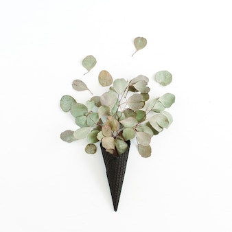 Cono di cialda gelato nero con foglie di eucalipto secco isolato su bianco