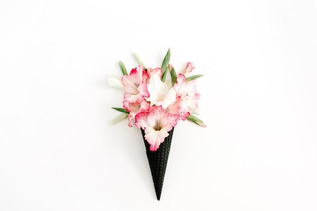 Cono di cialda gelato nero con fiori di gladiolo rosa secchi isolati su bianco