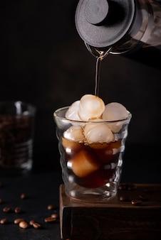 Il caffè nero ghiacciato viene versato in un bicchiere con ghiaccio, su uno sfondo nero