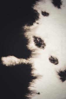 Inchiostro nero trasportato su carta bianca close-up. filtro scuro sfondo astratto. macchie di inchiostro sparse e assorbite nella carta macro.