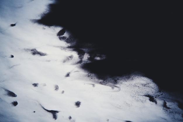 Inchiostro nero spalmato e assorbito su carta bianca da primo piano. filtro scuro sfondo astratto. macchie di inchiostro sparse e assorbite nella carta macro.