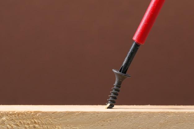Viti in ferro nero avvitate nel legno con un cacciavite.
