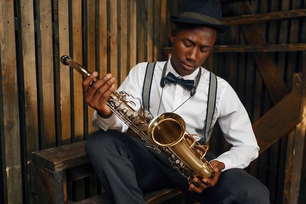 Musicista jazz nero seduto con il sassofono. il jazzista nero in cappello posa con lo strumento