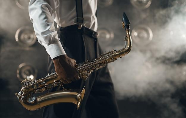 Musicista jazz nero con sassofono sul palco con fumo. il jazzista nero tiene lo strumento in mano