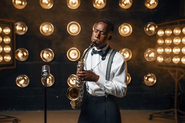Black jazz performer suona il sassofono sul palco con faretti. jazzman nero che si esibisce sulla scena