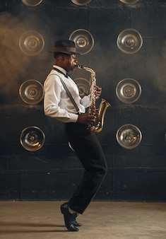 Il jazzista nero in cappello suona il sassofono sul palco con i riflettori. musicista jazz nero che si esibisce sulla scena