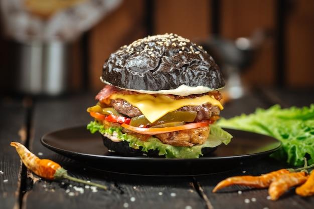 Hamburger succoso nero sulla tavola di legno del piatto scuro