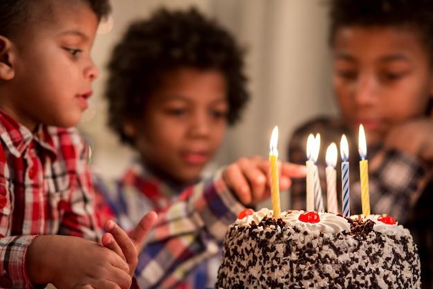 Ragazzo nero che tocca le torte con la candela ragazzo tocca la candela con le torte di compleanno fai attenzione, amico mio, non giocare con lo spirito...