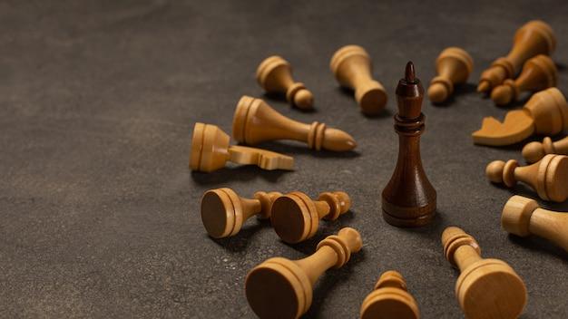 Re nero tra i pezzi degli scacchi bianchi su sfondo scuro