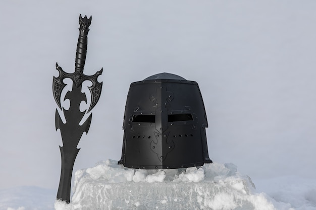 Elmo da cavaliere nero e spada sul ghiaccio