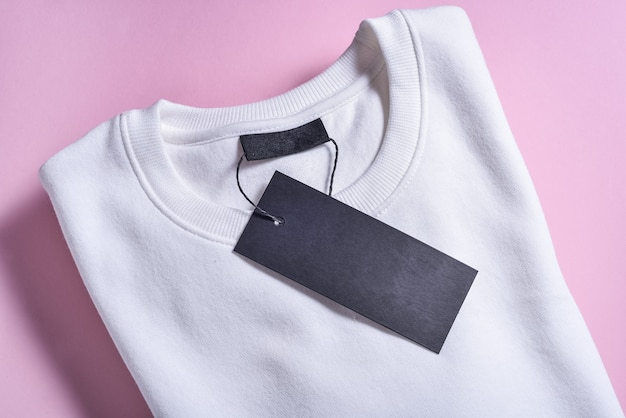 Etichetta nera della felpa sulla superficie rosa