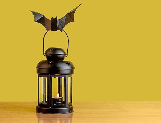 Sul tavolo c'è una lanterna nera. un pipistrello di carta nero siede sulla lanterna. decorazione per la vacanza.