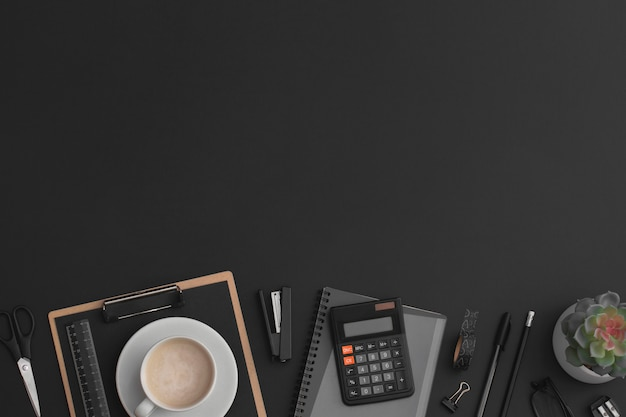 Tavolo da ufficio in pelle nera con calcolatrice, taccuino, tazza da caffè e pianta verde. vista dall'alto con copia spazio. composizione piatta.
