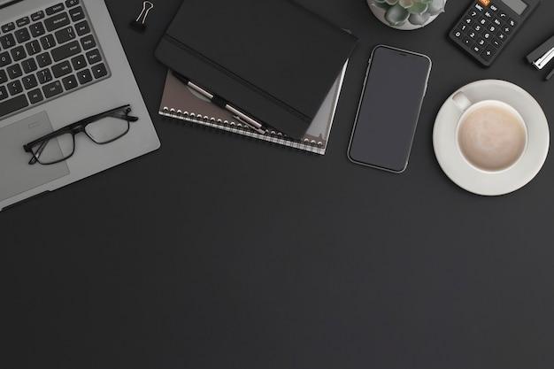 Tavolo da ufficio in pelle nera con calcolatrice, taccuino, tazza da caffè e pianta verde