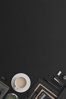 Tavolo da ufficio in pelle nera con tazza da caffè per notebook e pianta verde