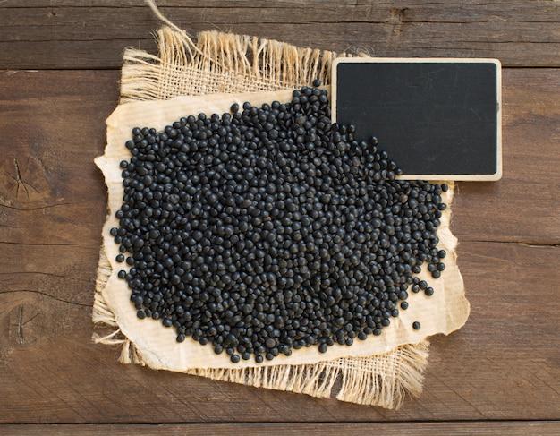Lenticchie nere con una piccola lavagna su una vista dall'alto di un tavolo in legno