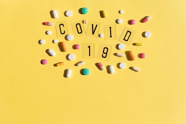 Le lettere nere sono allineate con la parola covid, le pillole con una mascherina medica. influenza, virus maschera protettiva, mascherina chirurgica. malattia di coronavirus. pillole colorate. vista dall'alto