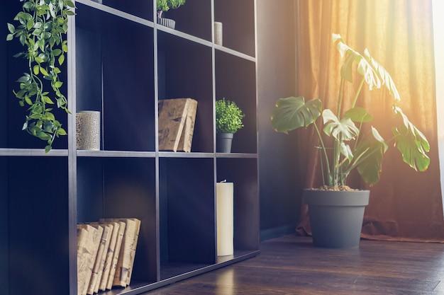 Cremagliera della decorazione interna del salone nero con piante di casa, mensole con piante, libri, candele.
