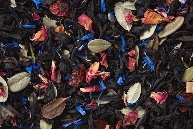 Texture di tè nero in foglie sciolte con frutta secca, erbe e petali di fiori