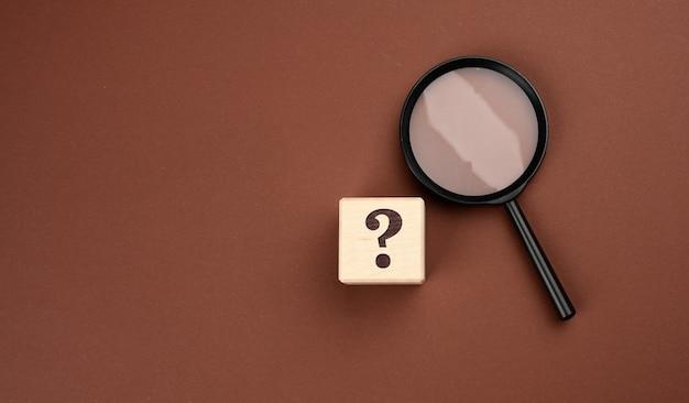 Lente d'ingrandimento nera su una superficie marrone e punti interrogativi. il concetto di incertezza e la ricerca di soluzioni, dubbi, flat lay