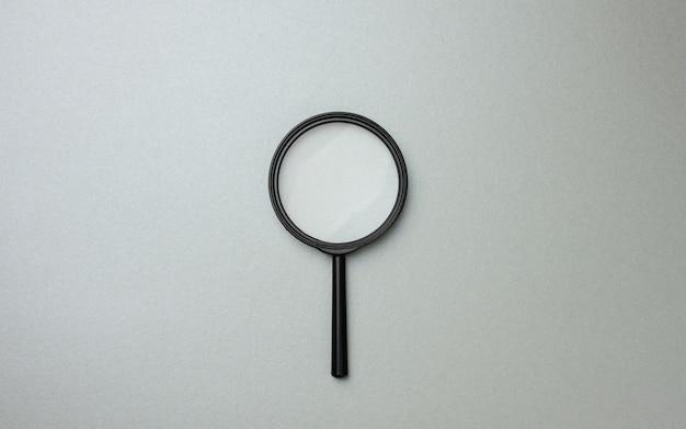 Lente d'ingrandimento nera su superficie grigia e punti interrogativi. il concetto di incertezza e la ricerca di soluzioni, dubbi, flat lay