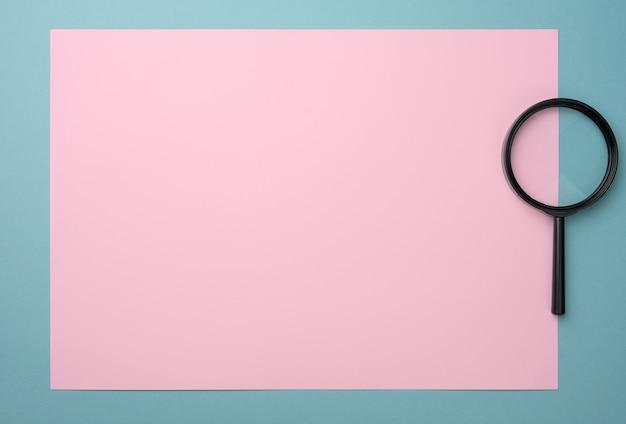 Lente d'ingrandimento nera su una superficie rosa-blu. il concetto di incertezza e la ricerca di soluzioni, dubbi, flat lay