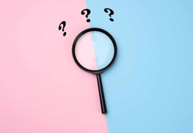 Lente d'ingrandimento nera su superficie rosa-blu e punti interrogativi. il concetto di incertezza e la ricerca di soluzioni, dubbi, flat lay