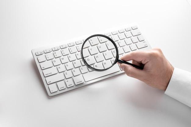 Lente di ingrandimento nero su una tastiera bianca su un bianco