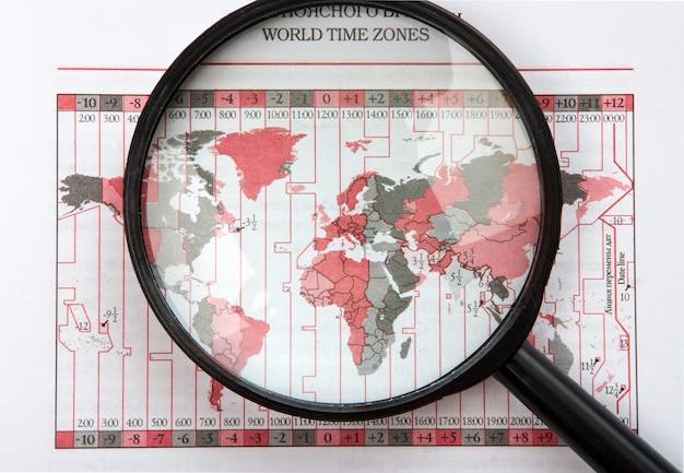 Lente d'ingrandimento nera sulla mappa del mondo con fusi orari