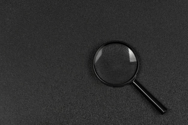 Lente d'ingrandimento nera su sfondo nero. lente di ingrandimento. ricerca