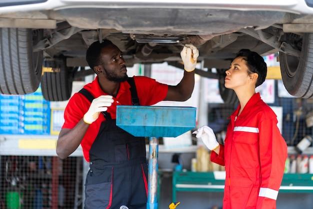 Nero maschio e femmina apprendista meccanici che lavorano sotto auto insieme manutenzione auto e garage di servizio auto.