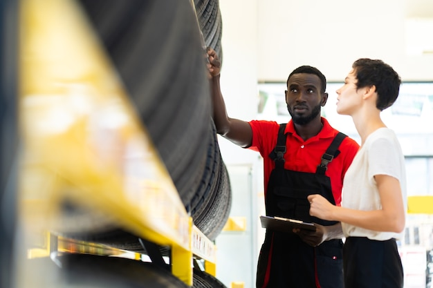Venditore maschio nero che mostra i pneumatici delle ruote al cliente donna caucasica al servizio di riparazione auto e negozio di auto.