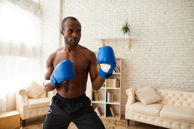 L'uomo di colore in guantoni da boxe è in piedi in posizione di combattimento.