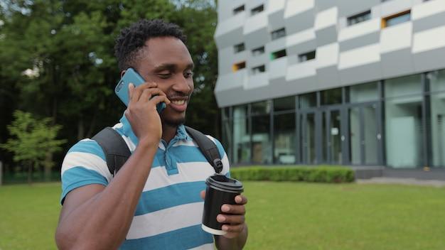 Uomo di colore in abiti casual che trasportano borsa sulla spalla e chiacchierano sui social media mentre camminano per strada in città sorseggiando una bevanda calda per andare a parlare su smartphone mentre si cammina per strada