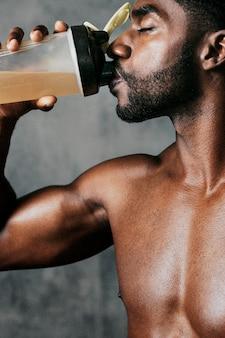 Uomo di colore che beve bevanda energetica