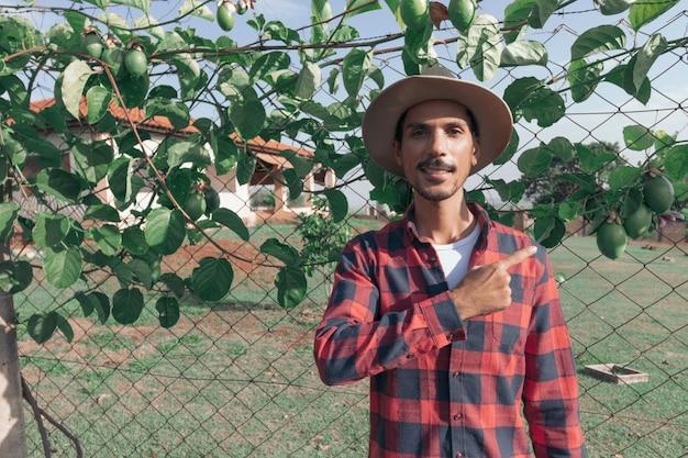 Agricoltore dell'uomo di colore in cappello in fattoria, pianta del frutto della passione sullo sfondo. spazio per il testo.