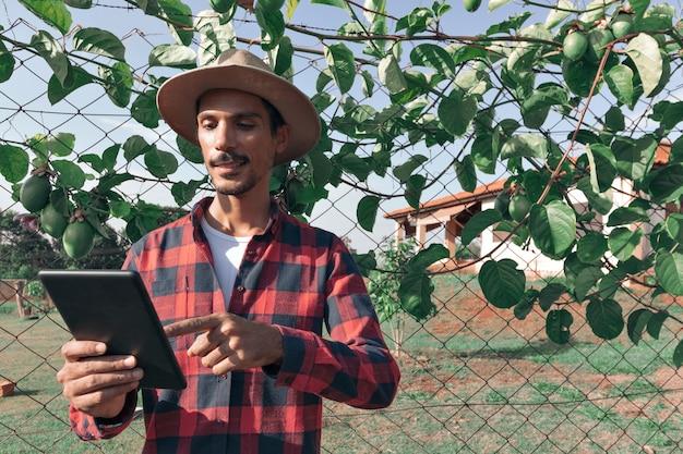 Agricoltore dell'uomo di colore che tiene una compressa con il cappello sull'azienda agricola, pianta del frutto della passione nel fondo