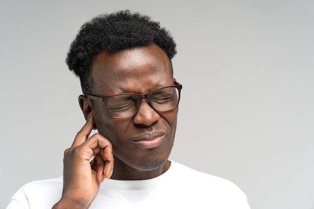 Uomo di colore accigliato che soffre di tinnito palpitante mal d'orecchi stanco del rumore che tocca l'orecchio doloroso