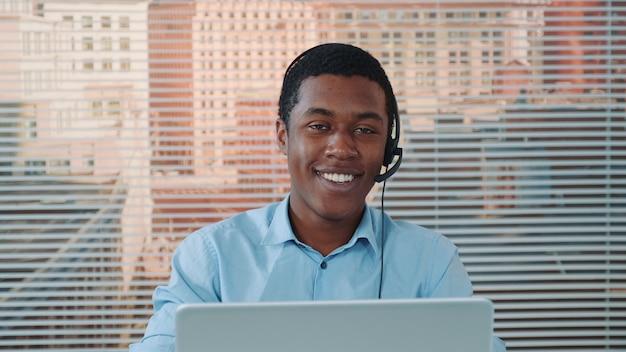 Uomo di colore in cuffia parlando con qualcuno e lavorando sul computer
