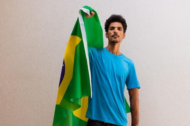 Uomo di colore che tiene una bandiera del brasile isolata su bianco. bandiera e immagine del concetto di festa dell'indipendenza.