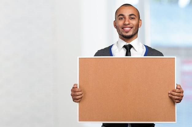 Uomo di colore che tiene una scheda del sughero