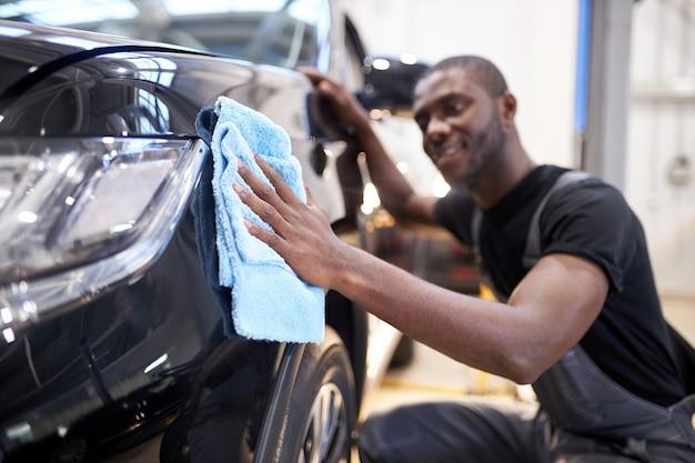L'uomo nero tiene in mano la microfibra e lucida l'auto in servizio di auto